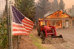 """A red tractor is left behind as a home burns outside of Taylorsville in Plumas County, Calif., that was impacted by the Dixie Fire Friday, Aug. 13, 2021. The U.S. Forest Service said Friday it's operating in crisis mode, fully deploying firefighters and maxing out its support system as wildfires continue to break out across the U.S. West. The agency says it has more than twice the number of firefighters working on the ground than at this point a year ago, and is facing """"critical resources limitations."""" An estimated 6,170 firefighters alone are battling the Dixie Fire in Northern California, the largest of 100 large fires burning in 14 states, with dozens more burning in western Canada. It has destroyed more than 1,000 structures in the northern Sierra Nevada. (AP Photo/Eugene Garcia)"""