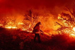 A firefighter battles the Dixie Fire as it jumps Highway 395, south of Janesville in Lassen County, Calif., on Monday, Aug. 16, 2021. Critical fire weather throughout the region has spread multiple wildfires burning in Northern California. (AP Photo/Noah Berger)