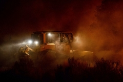 A dozer works to contain the Dixie fire as it jumps Highway 395 south of Janesville, Calif., on Monday, Aug. 16, 2021. Critical fire weather throughout the region threatens to spread multiple wildfires burning in Northern California. (AP Photo/Ethan Swope)