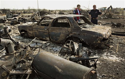 FILE - In this May 13, 2016 file photo, Canadian Prime Minister Justin Trudeau, left, and Fort McMurray Fire Chief Darby Allen look over a burnt out car during a visit to Fort McMurray, Canada. Canada's central bank says the Canadian economy will shrink and become much weaker than expected because of Alberta's devastating wildfires, which shut down its oil sands production. The Bank of Canada, which kept its key interest rate on hold Wednesday, May 25, said its preliminary assessment is that the destruction and halt to oil production will knock about 1 1/4 percentage points off real GDP growth in the second quarter.(Jason Franson/The Canadian Press via AP) MANDATORY CREDIT