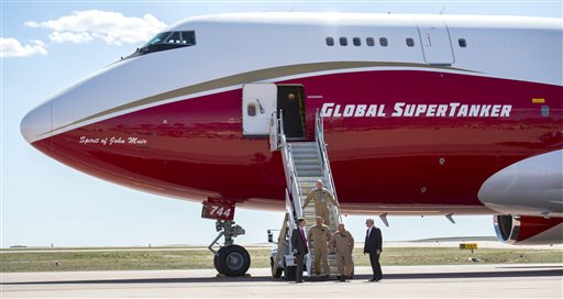 Colorado Gov. John Hickenlooper, left, greets the flight crew of the Boeing 747-400 Global SuperTanker after it dropped half its capacity of 19,400-gallons of water over the airfield during a ceremony Thursday, May 5, 2016, at the Colorado Springs, Colo., Airport demonstrating firefighting capabilities of the worldÂ's largest firefighting plane.  The Spirit of John Muir plane will be stationed out of the Colorado Springs Airport and will be able to respond to fires around the world.  (Christian Murdock/The Gazette via AP)