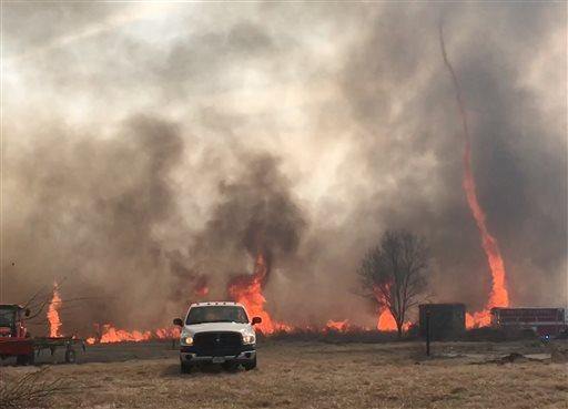 In this image made from a Feb. 18, 2016 video by Dean Cull, deputy chief of the Southern Platte Fire Protection District, a twisting fire, also known as a fire tornado, shoots up in the air as the grass fires spread on the field in Platte County, Mo. Firefighters in northwest Missouri are continuing to watch the site of a grass fire fueled by high winds that damaged up to 1,500 acres of land in Platte County. (Dean Cull/Southern Platte Fire Protection District via AP)