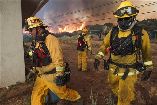 Lakeside firefighters Joe Vasquez, left, and David Csik walk around a house as Lakeside Fire Capt. Jon Jordan watches large flames burn toward the home on Highway 94 south of Potrero Calif., on Monday, June 20, 2016. An intensifying heat wave stretching from the West Coast to New Mexico threatened to make the fight against Southern California wildfires more difficult Monday. (Hayne Palmour IV/San Diego Union-Tribune via AP)