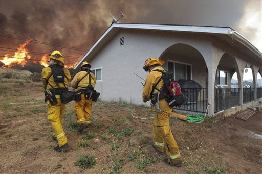 Lakeside firefighters walk next to a home on Highway 94 south of Potrero, Calif., as a wildfire burns near the home on Monday, June 20, 2016. An intensifying heat wave stretching from the West Coast to New Mexico threatened to make the fight against Southern California wildfires more difficult Monday. (Hayne Palmour IV/San Diego Union-Tribune via AP)