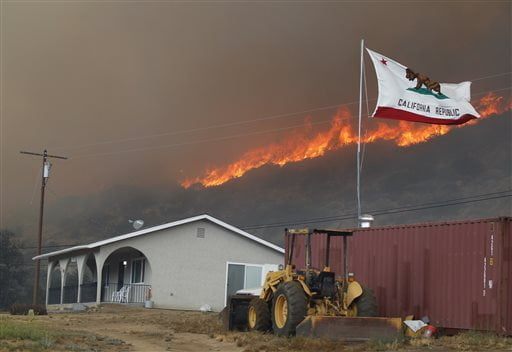 The California state flag flies next to a home on Highway 94 south Potrero, Calif., on Monday, June 20, 2016, as huge flames roar behind it. An intensifying heat wave stretching from the West Coast to New Mexico threatened to make the fight against Southern California wildfires more difficult Monday. (Hayne Palmour IV/San Diego Union-Tribune via AP)