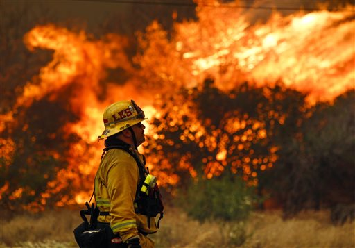 Lakeside firefighter Joe Vasquez watches as large flames burn next to a home on Highway 94 south of Potrero, Calif., on Monday, June 20, 2016. An intensifying heat wave stretching from the West Coast to New Mexico threatened to make the fight against Southern California wildfires more difficult Monday. (Hayne Palmour IV/San Diego Union-Tribune via AP)