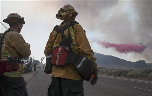 Two fire captains with the Loma Linda Fire Department watch as a tanker flies in low to drop fire retardant on a wildfire burning close to Highway 94 near Potrero, Calif., on Monday, June 20, 2016. (Hayne Palmour IV/San Diego Union-Tribune via AP)