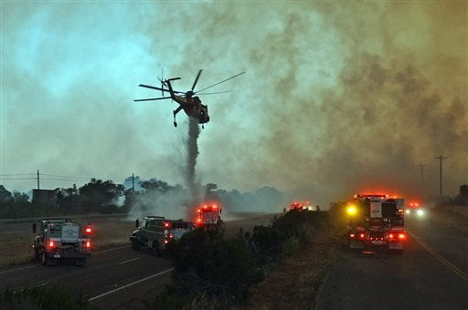 A skycrane helicopter makes an emergency water drop onto the US Highway 101 center divider near the El Capitan State Park Thursday, June 16, 2016.  Wind driven flames from the Sherpa Fire pushed down canyon and near the freeway. (Mike Eliason/Santa Barbara County Fire Department via AP)