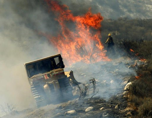 Firefighters create a firebreak as they work to stop the advance a wildfire near the town of Acton, Calif., Monday, July 25, 2016. A firefighting army converged Monday on a dangerous wildfire burning in the mountainous northern fringe of metropolitan Los Angeles after it wildly expanded and forced thousands of people from their homes during the weekend. (AP Photo/Nick Ut)