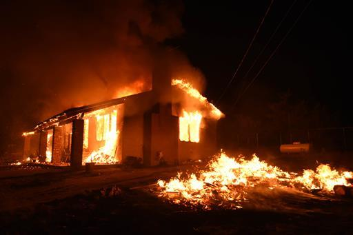 A home is fully engulfed in a fire caused by a fast burning wildfire in the section of South Lake near Lake Isabella, Calif. on Friday, June 24, 2016. Dozens of homes burned to the ground as a wildfire raged over ridges and tore through rural communities in central California, authorities said. (Ryan Babroff via AP)