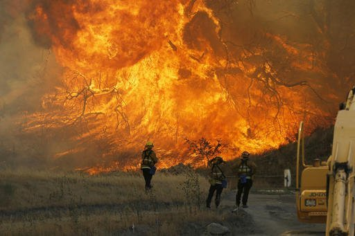 A hillside erupts in flame as a raging wildfire fire burns in Placerita Canyon in Santa Clarita, Calif., Monday, July 25, 2016. A raging wildfire that forced thousands from their homes on the edge of Los Angeles continued to burn out of control Monday as frustrated fire officials said residents reluctant to heed evacuation orders made conditions more dangerous and destructive for their neighbors.  (AP Photo/Nick Ut)