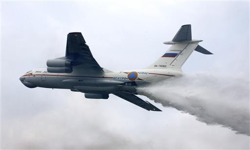 In this file photo taken on Friday, Sept. 27, 2002, an Il-76 jet releases clouds of fire-retardant chemicals during joint exercises of fire and rescue workers in Noginsk, some 68 kilometers (42 miles) east of Moscow, Russia. Russia's Emergencies Ministry said one of its firefighting planes with a crew of 10 has gone missing in Siberia. The ministry said the Il-76 plane disappeared Friday, July 1, 2016, while on a mission to fight forest fires in the Irkutsk region. The plane in this photo is the same model but not the one which went missing.(AP Photo/Maxim Marmur, File)