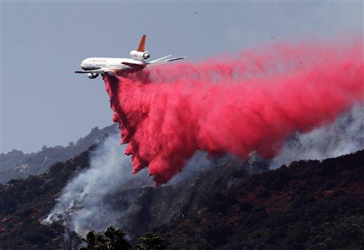 A DC-10 air tanker drops fire retardant in Duarte, Calif., on Wednesday . June 22, 2016. Twin fires have continued to burn in the San Gabriel Valley, northeast of Los Angeles. (AP Photo/Nick Ut)