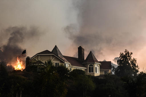 A wildfire burns close to a home near Sand Caynon and Placerita Caynon in Santa Clarita, Calif., Saturday, July 23, 2016. Hundreds of county and Angeles National Forest firefighters battled the blaze, aided by three dozen water-dropping helicopters and retardant-dropping airplanes. The fire erupted Friday afternoon in the Sand Canyon area of suburban Santa Clarita near State Route 14 as the region was gripped by high heat and very low humidity. Winds pushed it into the adjacent Angeles National Forest. (AP Photo/Ryan Babroff)