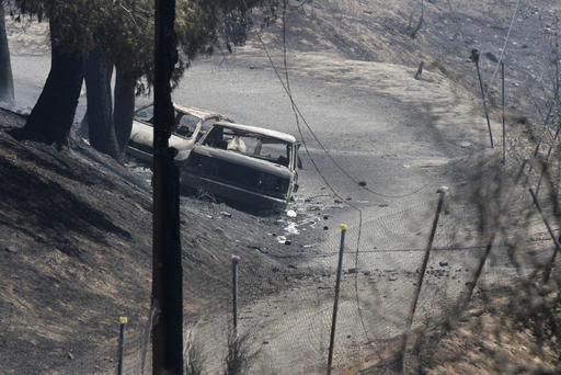Vehicles destroyed due to a wildfire are seen in Santa Clarita, Calif., Sunday, July 24, 2016. The body of a man was discovered Saturday in one of the vehicles outside a home in the fire zone. Los Angeles County sheriff's officials are investigating the death but said there was no evidence it was a crime. Which vehicle the body was found was not unclear at the time the photo was taken. (Katharine Lotze/The Santa Clarita Valley Signal via AP)