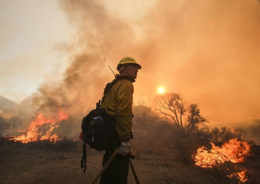 "A firefighter watches a wildfire near Placenta Caynon Road in Santa Clarita, Calif., Sunday, July 24, 2016. Flames raced down a steep hillside ""like a freight train,"" leaving smoldering remains of homes and forcing thousands to flee the wildfire churning through tinder-dry canyons in Southern California, authorities said Sunday. (AP Photo/Ringo H.W. Chiu)"