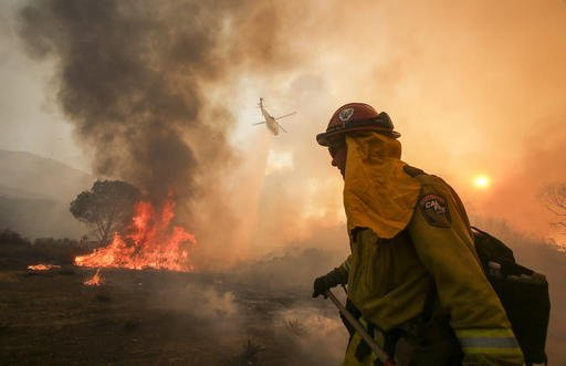 "A firefighter watches as a helicopter makes a drop on a wildfire near Placenta Caynon Road in Santa Clarita, Calif., Sunday, July 24, 2016. Flames raced down a steep hillside ""like a freight train,"" leaving smoldering remains of homes and forcing thousands to flee the wildfire churning through tinder-dry canyons in Southern California, authorities said Sunday. (AP Photo/Ringo H.W. Chiu)"