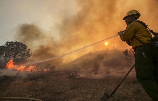 "A firefighter battles the wildfire near Placenta Caynon Road in Santa Clarita, Calif., Sunday, July 24, 2016. Flames raced down a steep hillside ""like a freight train,"" leaving smoldering remains of homes and forcing thousands to flee the wildfire churning through tinder-dry canyons in Southern California, authorities said Sunday. (AP Photo/Ringo H.W. Chiu)"