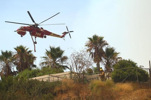"An Erickson Air-Crane takes off in Santa Clarita, Calif., Sunday, July 24, 2016. Flames raced down a steep hillside ""like a freight train,"" leaving smoldering remains of homes and warnings that more communities should be ready to flee the wildfire churning through tinder-dry canyons in Southern California, authorities said Sunday. (AP Photo/Matt Hartman)"