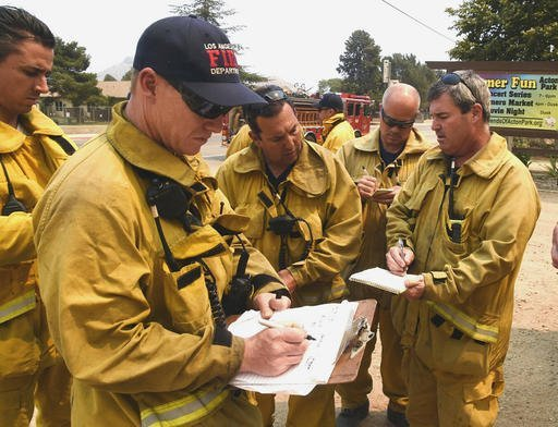 "Los Angeles County Fire Battalion Chief Gary Harris, right, discusses structure protection assignments with Santa Clarita firefighters at Acton Park in Santa Clarita, Calif., on Sunday, July 24, 2016. Flames raced down a steep hillside ""like a freight train,"" leaving smoldering remains of homes and warnings that more communities should be ready to flee the wildfire churning through tinder-dry canyons in Southern California, authorities said Sunday. (Dan Watson/The Santa Clarita Valley Signal via AP)"