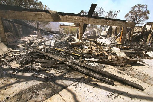 "The remains of a burned home smolder in Iron Canyon Road area near Santa Clarita, Calif., Sunday, July 24, 2016. Flames raced down a steep hillside ""like a freight train,"" leaving smoldering remains of homes and warnings that more communities should be ready to flee the wildfire churning through tinder-dry canyons in Southern California, authorities said Sunday. (AP Photo/Matt Hartman)"