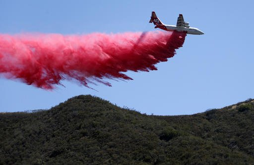 A plane drops fire retardant on an unburned ridge in advance of flames as a wildfire fire burns in Placerita Canyon in Santa Clarita, Calif., Monday, July 25, 2016. A raging wildfire that forced thousands from their homes on the edge of Los Angeles continued to burn out of control Monday as frustrated fire officials said residents reluctant to heed evacuation orders made conditions more dangerous and destructive for their neighbors. (AP Photo/Nick Ut)