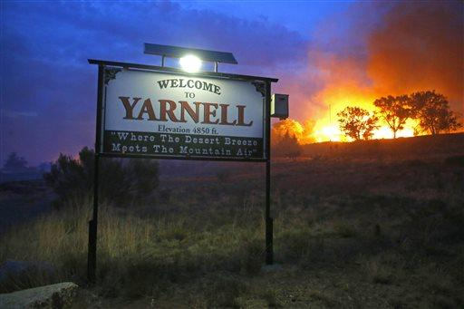 In this June 30, 2013 file photo, a wildfire burns homes in Yarnell, Ariz. The wildfire that began with a lightning strike and caused little immediate concern because of its remote location and small size quickly blazed into an inferno, leading officials to rapidly order more resources in the hours before flames killed 19 members of an elite Hotshot crew, according to a report released Monday, July 15, 2013. (AP Photo/The Arizona Republic, David Kadlubowski, File)