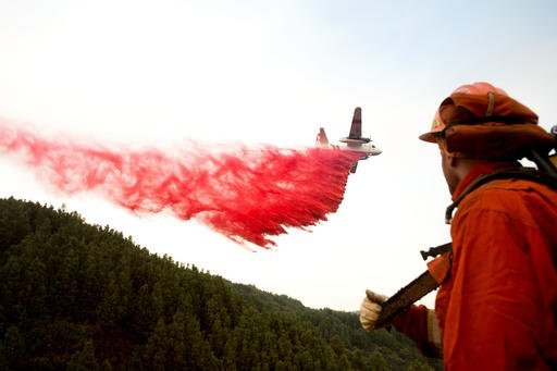 An inmate firefighter watches as an air tanker drops retardant while battling a wildfire near Morgan Hill, Calif., on Wednesday, Sept. 28, 2016. A growing and destructive wildfire moved toward remote California homes in the Santa Cruz Mountains on Wednesday as it scorched its way through bone-dry brush and trees. (AP Photo/Noah Berger)