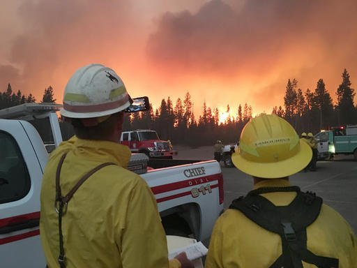 In this Sunday, Sept. 11, 2016, photo provided by the National Park Service, firefighters observe a wildfire's push to the northeast, after initiating sprinkler systems to protect structures around Headwaters Lodge at Flagg Ranch in Moran, Wyo. A wildfire that roared back to life closed the south gate to Yellowstone National Park again Monday, Sept. 12, 2016 and forced employees to flee. The same blaze shut down the entrance for nine days late last month. The fire had died down until winds picked up Sunday, taking firefighters by surprise. Authorities closed U.S. 89/191/287 between the Lizard Creek Campground in Grand Teton National Park and Lewis Lake in Yellowstone. (Scott Guenther/National Park Service via AP)
