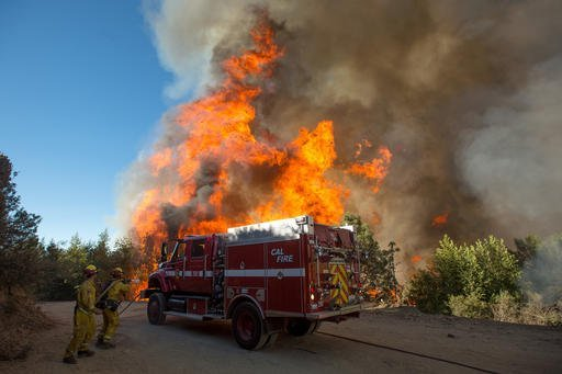 Flames from a wildfire tower above firefighters as they try to stop the blaze from crossing Loma Prieta Ave. near Morgan Hill, Calif., on Tuesday, Sept. 27, 2016. (AP Photo/Noah Berger)