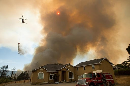 A helicopter drops water as the Loma fire approaches a home near Morgan Hill, Calif., on Tuesday, Sept. 27, 2016. (AP Photo/Noah Berger)