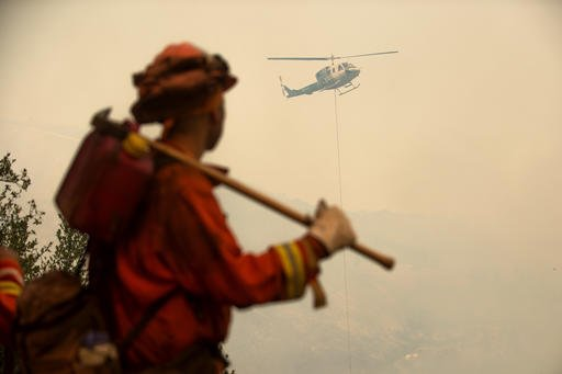 An inmate firefighter watches a helicopter drop water on the Loma fire burning near Morgan Hill, Calif., on Tuesday, Sept. 27, 2016. (AP Photo/Noah Berger)