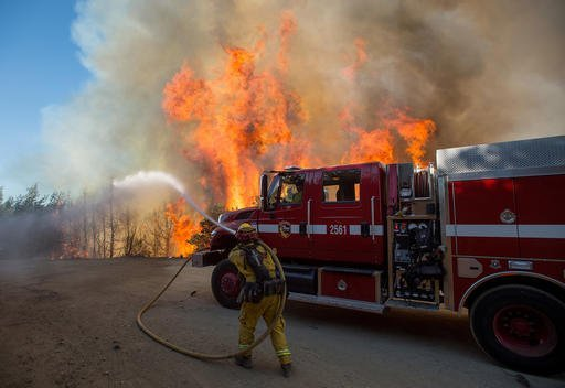 Flames from a wildfire tower above a firefighter as he tries to stop the blaze from crossing Loma Prieta Ave. near Morgan Hill, Calif., on Tuesday, Sept. 27, 2016. (AP Photo/Noah Berger)