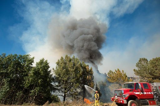 Smoke from a wildfire rises above a firefighter as he tries to stop the blaze from crossing Loma Prieta Ave. near Morgan Hill, Calif., on Tuesday, Sept. 27, 2016. A heat wave stifling drought-stricken California has worsened a wildfire that burned some buildings and forced people from their homes in remote communities along the Santa Cruz Mountains. (AP Photo/Noah Berger)