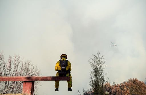 Firefighter Capt. Chris Zinko takes a break while battling a wildfire near Morgan Hill, Calif., on Tuesday, Sept. 27, 2016. A heat wave stifling drought-stricken California has worsened a wildfire that burned some buildings and forced people from their homes in remote communities along the Santa Cruz Mountains. (AP Photo/Noah Berger)
