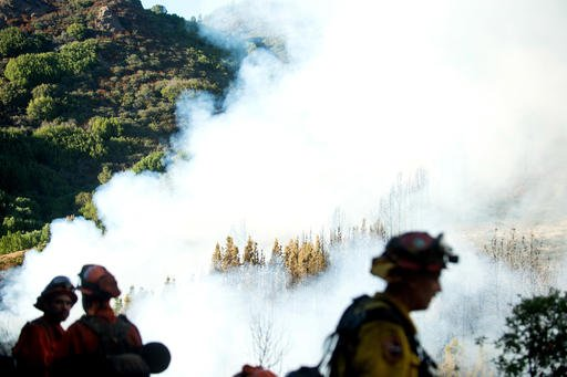 Firefighters watch as smoke from a wildfire swirls around a stand of trees near Morgan Hill, Calif., Tuesday, Sept. 27, 2016. A heat wave stifling drought-stricken California has worsened a wildfire that burned some buildings and forced people from their homes in remote communities along the Santa Cruz Mountains. (AP Photo/Noah Berger)