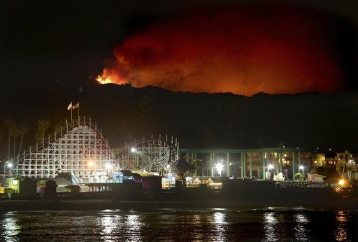 In this photo taken Tuesday, Sept. 27, 2016, the Loma Fire rages on the Santa Cruz Mountains summit beyond the Giant Dipper Roller Coaster in Santa Cruz, Calif. More California residents were ordered from their homes Tuesday as a growing wildfire threatened remote communities in the Santa Cruz Mountains. The blaze in a rugged area about 30 miles south of San Jose destroyed one home and charred more than 1.5 square miles of dry brush and timber, according to the California Department of Forestry and Fire Protection. (Shmuel Thaler/The Santa Cruz Sentinel via AP)