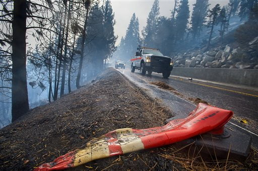 CalTrans road crews drive past a melted traffic cone at the Emerald Fire along Highway 89, Friday, Oct. 14, 2016 on the southwest shores of Lake Tahoe. The blaze that burned about 200 acres northwest of South Lake Tahoe, California was one of three wind-whipped wildfires burning along the Sierra Nevada. The largest one destroyed more than 20 homes in a rural valley between Carson City and Reno, Nevada. (Randall Benton/The Sacramento Bee via AP)