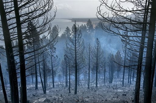 Lake Tahoe can be seen behind the Emerald Fire along Highway 89, Friday, Oct. 14, 2016 on the southwest shores of Lake Tahoe. The blaze that burned about 200 acres northwest of South Lake Tahoe, California was one of three wind-whipped wildfires burning along the Sierra Nevada. The largest one destroyed more than 20 homes in a rural valley between Carson City and Reno, Nevada. (Randall Benton/The Sacramento Bee via AP)