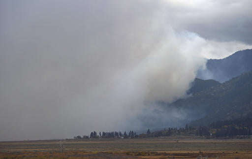 Smoke rises from a wildfire along the eastern slope of the Sierras, Friday, Oct. 14, 2016, in Washoe Lake, Nev. Officials say the wind-whipped wildfire is raging out of control in northern Nevada and has destroyed more than a dozen homes, forced evacuations, closed roads and schools, and triggered power outages. (Andy Barron/The Reno Gazette-Journal via AP)