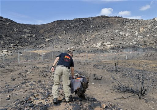 In this July 23, 2013 file photo, Prescott Wildland Division Chief Darrell Willis touches A Granite Mountain Hot Shots crew shirt draped over a burned cactus, in Yarnell, Ariz. Arizona Gov. Doug Ducey plans to dedicate a long-awaited memorial for the 19 Granite Mountain Hotshots who perished in a wildfire three years ago. Ducey will be joined by family members of the fallen firefighters on Tuesday, Nov. 29, 2016, at a private dedication of the Granite Mountain Hotshots Memorial State Park. (AP Photo/Matt York, File)