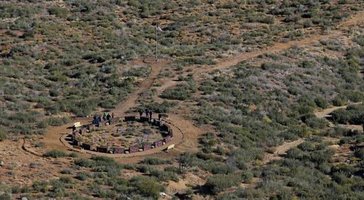 A few family members, fellow firefighters, and park officials gather around a memorial at the end of a four mile trail that was officially opened, dedicating the new Granite Mountain Hotshots Memorial State Park as a tribute to the 19 firefighters killed during a 2013 wildfire, during a ceremony Tuesday, Nov. 29, 2016, in Yarnell, Ariz. The park was dedicated after Arizona's state Legislature spent $500,000 in 2014 to buy the land and the nearly 3-mile trail was built from a state highway to the spot where the flames trapped the firefighters. (AP Photo/Ross D. Franklin)