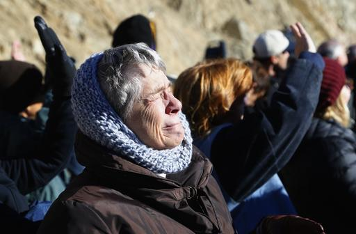A family member is overcome as she watches a missing man formation of fire fighting planes as they fly over during a dedication ceremony for the new Granite Mountain Hotshots Memorial State Park as a tribute to the 19 firefighters killed during a 2013 wildfire Tuesday, Nov. 29, 2016, in Yarnell, Ariz. Gov. Doug Ducey said the 3-mile trail and memorial would serve as a lasting tribute to the fallen firefighters' heroism.(AP Photo/Ross D. Franklin)