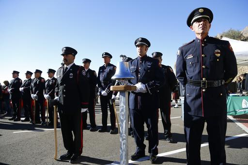 Firefighters from a variety of honor guards from around Arizona attend stand at attention during a dedication ceremony for the new Granite Mountain Hotshots Memorial State Park as a tribute to the 19 firefighters killed during a 2013 wildfire Tuesday, Nov. 29, 2016, in Yarnell, Ariz. Gov. Doug Ducey said the 3-mile trail and memorial would serve as a lasting tribute to the fallen firefighters' heroism.(AP Photo/Ross D. Franklin)