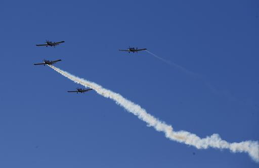 A missing man formation of fire fighting planes fly over a dedication ceremony for the new Granite Mountain Hotshots Memorial State Park as a tribute to the 19 firefighters killed during a 2013 wildfire Tuesday, Nov. 29, 2016, in Yarnell, Ariz. (AP Photo/Ross D. Franklin)