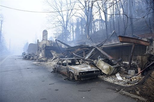 A structure and vehicle are damaged from the wildfires around Gatlinburg, Tenn., on  Tuesday, Nov. 29, 2016.  Rain had begun to fall in some areas, but experts predicted it would not be enough to end the relentless drought that has spread across several Southern states and provided fuel for fires now burning for weeks in states including Tennessee, Georgia and North Carolina. (Michael Patrick/Knoxville News Sentinel via AP)