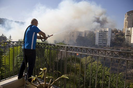 A man uses water to extinguish in wildfires in Haifa, Israel, Thursday, Nov. 24, 2016. Israeli police have arrested four Palestinians in connection with one of several large fires that damaged homes and prompted the evacuation of thousands of people in the past few days. Police are investigating the causes, including possible arson. Windy and hot weather have helped fan the flames. The blazes started three days ago near Jerusalem and in the north. Hundreds of homes were damaged. Russia, Italy and other countries are assisting the Israeli firefighters. (AP Photo/Ariel Schalit)