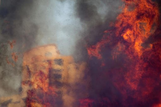 A wildfire rages in Haifa, Israel, Thursday, Nov. 24, 2016. The blaze ripped through parts of Israel's third-largest city, forcing tens of thousands of people to evacuate their homes and prompting a rare call-up of hundreds of military reservists to join overstretched police and firefighters. Spreading quickly due to dry, windy weather, the fire quickly spread through Haifa's northern neighborhoods. While there were no serious injuries, several dozen people were hospitalized for smoke inhalation. (AP Photo/Ariel Schalit)
