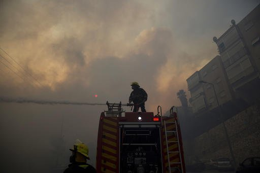 Firefighters fight wildfires in Haifa, Israel, Thursday, Nov. 24, 2016. A raging wildfire ripped through parts of Israel's third-largest city on Thursday, forcing tens of thousands of people to evacuate their homes and prompting a rare call-up of hundreds of military reservists to join overstretched police and firefighters. Spreading quickly due to dry, windy weather, the fire quickly spread through Haifa's northern neighborhoods. While there were no serious injuries, several dozen people were hospitalized for smoke inhalation. (AP Photo/Ariel Schalit)