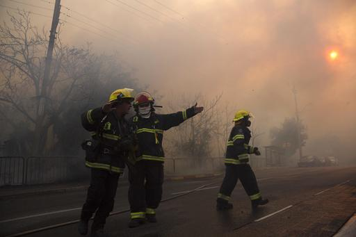 Firefighters work in Haifa, Israel, Thursday, Nov. 24, 2016. A raging wildfire ripped through parts of Israel's third-largest city on Thursday, forcing tens of thousands of people to evacuate their homes and prompting a rare call-up of hundreds of military reservists to join overstretched police and firefighters. Spreading quickly due to dry, windy weather, the fire quickly spread through Haifa's northern neighborhoods. While there were no serious injuries, several dozen people were hospitalized for smoke inhalation. (AP Photo/Ariel Schalit)